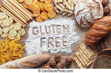Gluten free food. Various pasta, bread and snacks on wooden background from top view