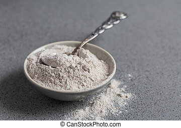 Glutenfree buckwheat flour for baking in the bowl on grey background