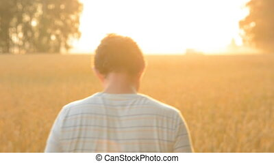 Go farmer on the wheat field. Adult man against a ripe crop...