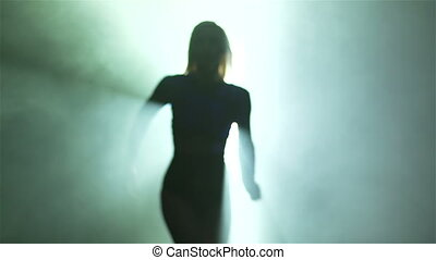 Slow-motion of a backlit go-go dancer running towards the camera and performing with passion