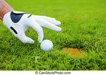Go in! Close-up of male hand in golf glove touching golf ball laying near the hole