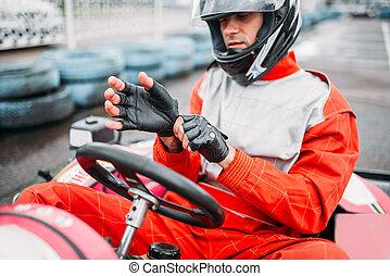 Go-kart driver in helmet on karting speed track. Carting...
