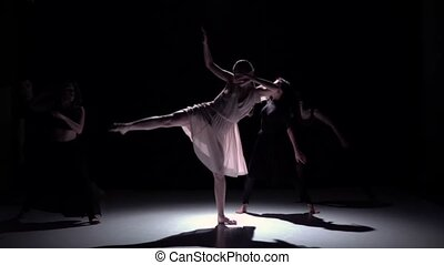 Go on contemporary dance of five dancers on black, shadow, slow motion