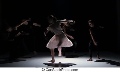 Go on of contemporary dance performance of five dancers on black, shadow