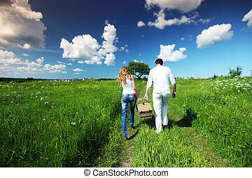 go on picnic - man and woman walk on picnic in green grass