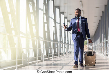 Go on plane. Businessman carrying luggage, moving to boarding gate in Airport