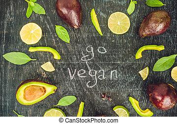 Go vegan concept with lettering. variety of fresh green organic vegetables lentils on dark background. Vegan food concept.