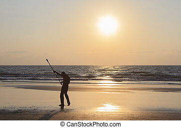 Unidentified man spinning pole on the beach.