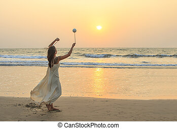 Unidentified woman spinning poi on the beach.