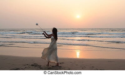 woman spinning poi on the beach.