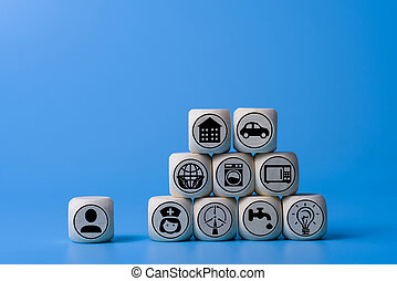 Goal achievement concept with icons on wooden cubes, blue background.