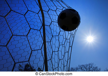 Goal. silhouette of soccer ball in a net with  blue sky and sun background