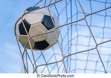 Goal - soccer or football ball in the net against blue sky.