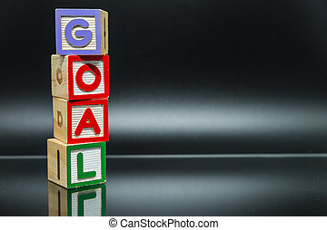 GOAL word wooden block arrange in vertical style on black background and selective focus