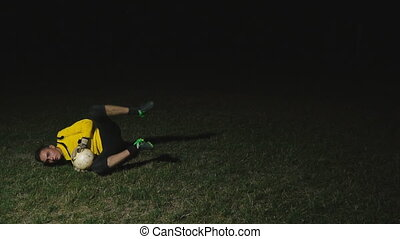 goalkeeper catches the ball on a black background