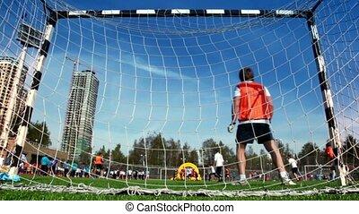 Goalkeeper in gate at football game on stadium, summer sunny...