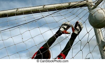 Goalkeeper in red letting in a goal during a game in slow ...