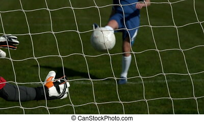 Goalkeeper in red saving a goal