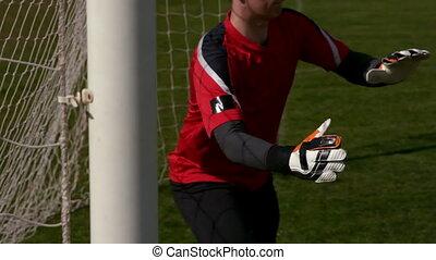 Goalkeeper in red saving a goal
