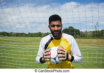 Goalkeeper with ball standing in front of goal post