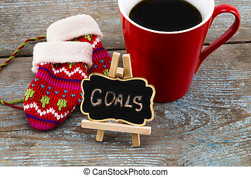 Goals - handwriting message on blackboard with a Cup of coffee and mittens, New Year resolutions concept