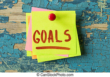 GOALS text written on sticky note on wooden background