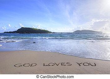 God Loves You written in sand on beach