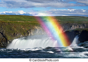 Godafoss waterfall and rainbow on a sunny day