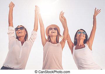 godere, life., vista angolare bassa, di, tre, bello, giovani donne, tenere mani, e, innalzamento, loro, braccia