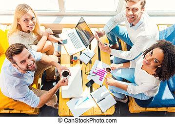 godere, loro, creativo, occupation., vista superiore, di, fourcheerful, giovani persone, lavorare insieme, mentre, seduta, a, il, scrivania legno, insieme