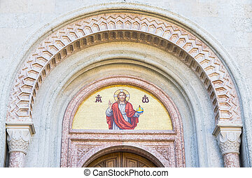 God's image mosaic above the doorway of a church.