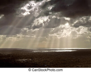 Clouds looming over the horizon with rays seeping through cast
