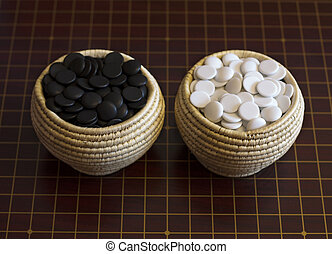 Goe boardgame. Bamboo baskets with stones for game go on wood. Strategy playing. Logical style photo.