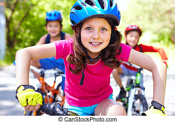 Going ahead - Portrait of a little girl riding her bike ...