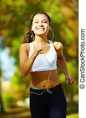 Going in for sport - portrait of a young woman jogging and...