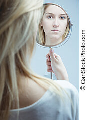 Close-up of a young, upset woman looking in the mirror she is holding in her hand