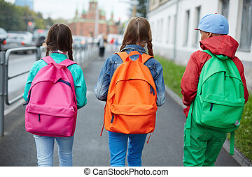 Going to school - Backs of schoolkids with colorful...