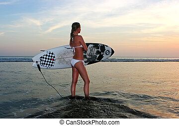 Going to surf? - Young lady going to surf at sunset
