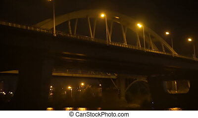 Going under the bridge at night, lights of passing cars