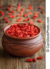 goji berries in a clay bowl on a wooden background