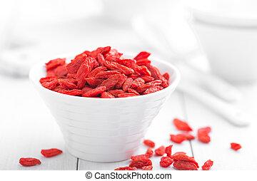 Goji berries in bowl on white background