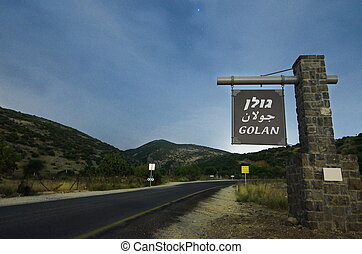"""Star lighted road leading to the Golan Heights in Israel bordering Syria and Lebanon, with a sign welcoming visitors to the """"Golan"""""""