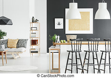 Gold accent in contrast color interior with white lamps above wooden countertop and black bar stools