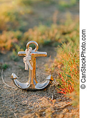 gold anchor on the grass