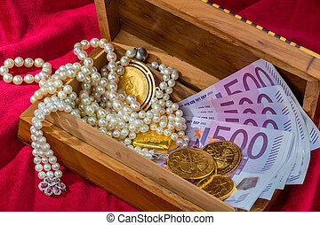 gold and jewelry - gold coins and bars with decorations on...