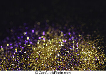Gold and purple glitter on black background with selective ...