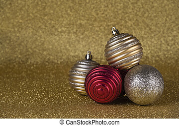 gold and red Christmas balls on a golden background of glitter
