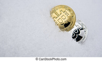 Gold and silver bitcoin. Cryptocurrency on snow, in the background. The concept of freelancing, the stock exchange. Gold bitcoin on cold winter snow background. Frozen bitcoin. Frozen account.
