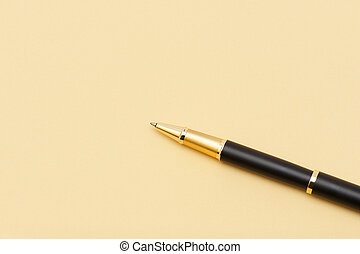 Gold ball pen on a yellow sheet of paper - Gold ball pen