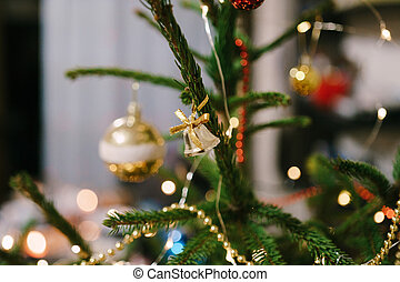 Gold bell with a bow on the branches of the Christmas tree.